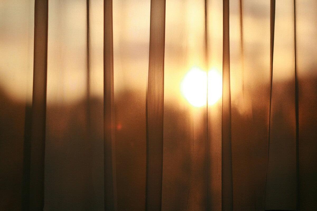 солнце просвечивает через шторы